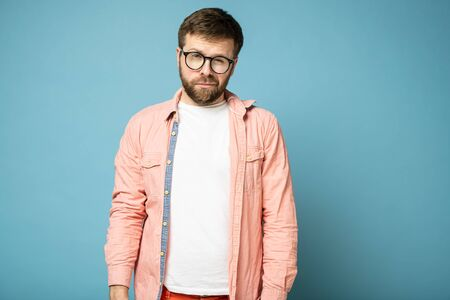 Handsome, calm, bearded man with glasses narrowed eyes and looks at the camera suspiciously.