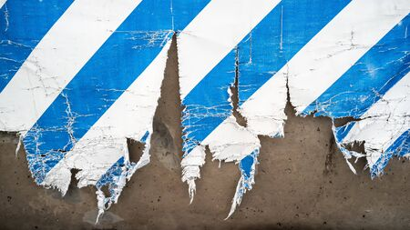 Torn white-blue, striped banner made of tarpaulin, on a concrete wall. Background. Texture.