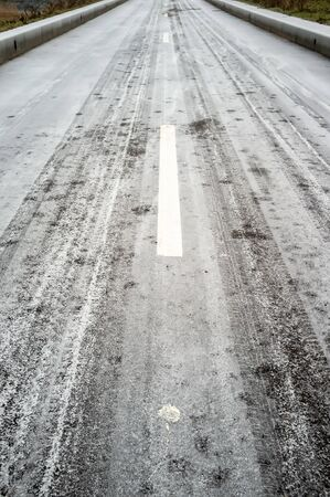 Frozen asphalt road with markings, curbs and sidewalks, in fog, on a cold winter day.