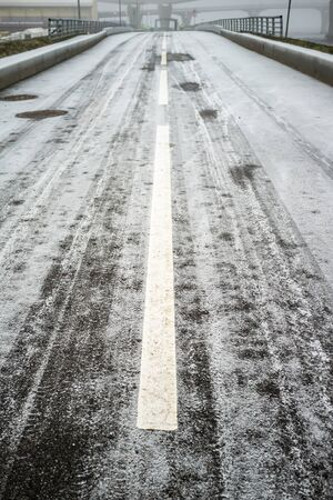 Frozen asphalt road with markings, borders and sidewalks, on the background of the bridge and viaduct, on a foggy, cold winter day.