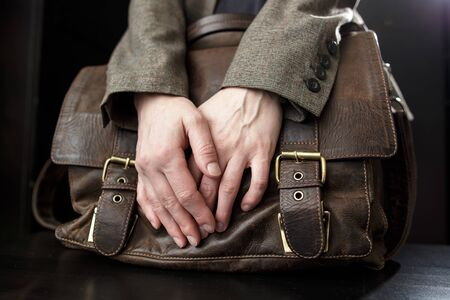 Teacher holds an old, brown, classic, leather briefcase with metal buckles, which stands on a table on a black background. Close-up.