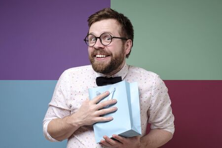 Man received a pleasant surprise, he is happy, joyfully presses a package with a gift to chest, smiles and looks at the camera.