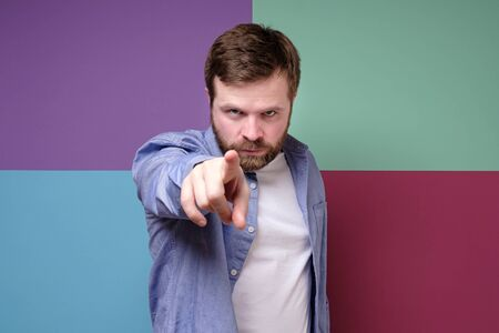 Bearded man with a stern look, makes a stop gesture with his index finger and tries to calm someone. Stock Photo