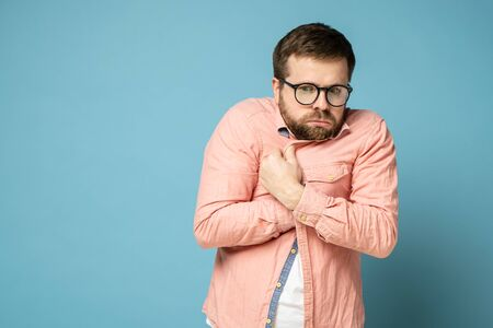 Bearded man in round glasses was offended, he squeezed shoulders, wrapped himself in a shirt and looked thoughtfully, anxiously.