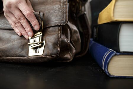 Hand fastens a buckle on an old brown, leather briefcase, which stands on a table next to books. Close-up. 免版税图像