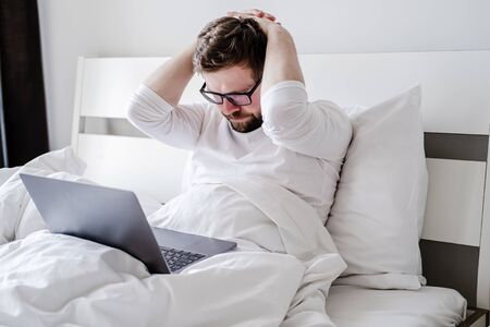 Man in pajamas is upset, he worked all night with a laptop in bed and did not finish the project, he holds hands behind head and looks thoughtfully at the screen.