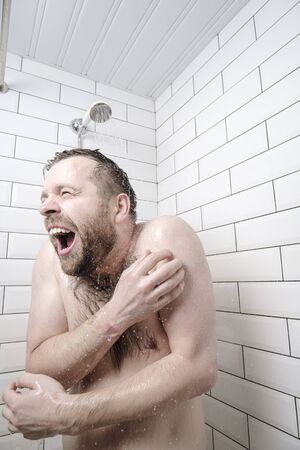 Funny bearded man feels shocked by taking a cold shower, he froze, screams and tries to close his body with hands. 版權商用圖片