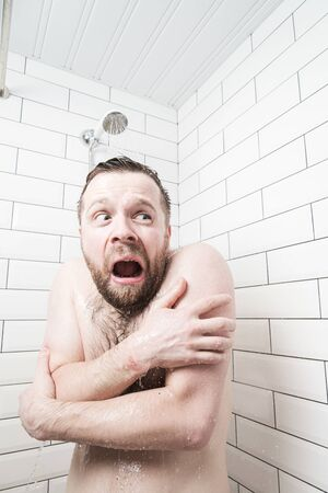 Man with a stupid expression on his face feels shocked at taking a cold shower, he froze and screams, covering his body with hands 版權商用圖片