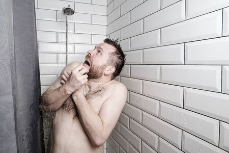 Shocked man looks at a watering can in the shower room, from which, unexpectedly, cold water is pouring.