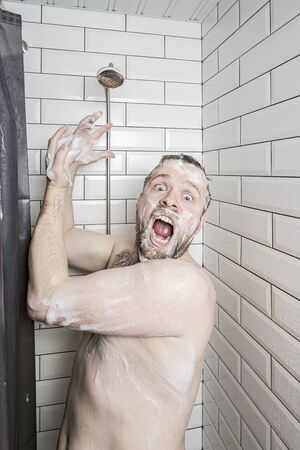 Shocked man in soapy foam screams and asks for help, because the soul has run out of water or something has broken. 版權商用圖片
