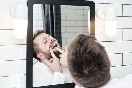 Man looks in the mirror, he opened mouth and examines the absence of a tooth that the dentist recently removed.