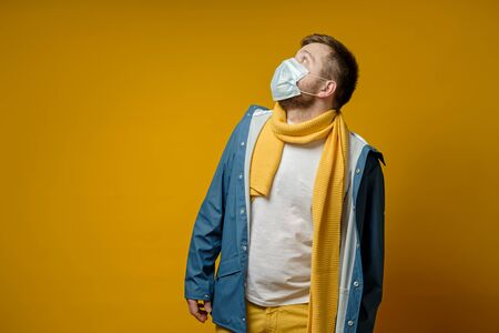 Man in a medical mask, in a scarf and jacket, fearfully looks upstairs, with copy space. Concept of the spread of the virus. Isolated on a yellow background.