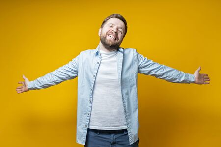 Beautiful, happy man stands with open arms, smiles and looks at the camera, on a yellow background. Stock fotó
