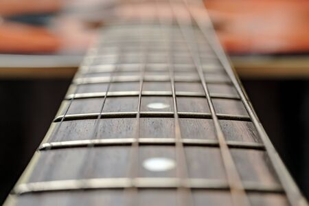 Neck with strings, close-up, on an old, classic acoustic guitar, under natural lighting.