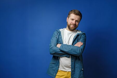 Modest, calm man stands with arms crossed, looking at the camera and smiling cute, with copy space, on a blue background.