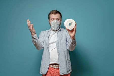 Man in a medical mask is happy, he bought toilet paper during a shortage of goods related to the epidemic of the virus. Paranoia.
