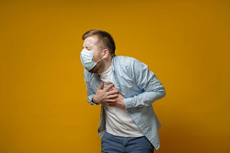 Man in a medical mask coughs, holds hands on chest, experiencing pain and closes eyes from suffering. Concept of the spread of the virus. Isolated on a yellow background.