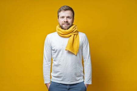 Attractive bearded man in a knitted scarf stands with hands folded in pockets and looks with a cute smile, on a yellow background.