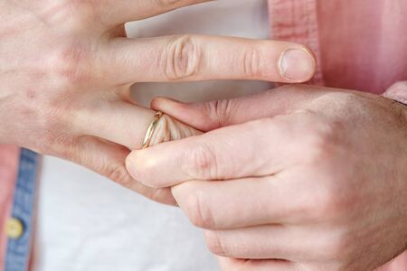 Man removes a gold wedding ring from his finger. Concept of family quarrel, divorce or betrayal.
