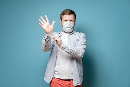 Man in a medical mask puts on latex gloves, he is confident that he was able to protect himself from a virus. Health concept. Standard-Bild