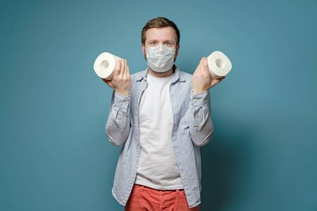 Joyful man in a medical mask holds in hands toilet paper, which he managed to buy during a virus outbreak and a shortage of goods.