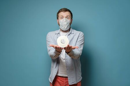 Man in a medical mask holding toilet paper on palms and looking joyfully. Concept of shortage of goods during a virus epidemic.