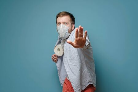 Man in a medical mask hides toilet paper under shirt and makes a stop gesture with hand. Concept of quarantine and paranoia.