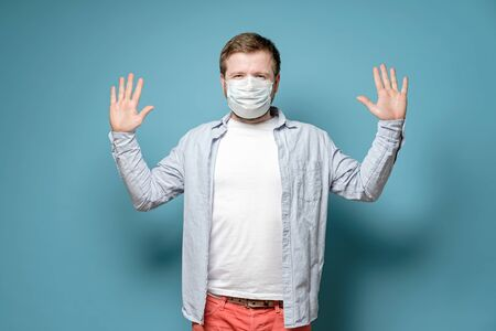 Man in a medical mask wants to avoid the spread of the virus when touched and raises hands. Health concept. Standard-Bild