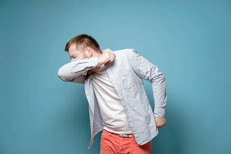 Caucasian man in medical mask coughs in his elbow. Correct sneezing. Concept of the spread of the virus.