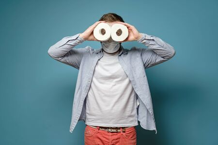 Man in a medical mask looks in two rolls of toilet paper like binoculars. Concept of shortage of goods during a virus outbreak.