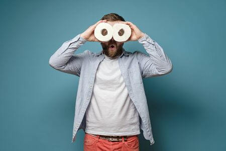 Surprised man holds two rolls of toilet paper in hands and looks at them like binoculars. Quarantine concept.