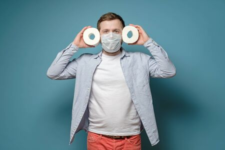 Satisfied man in a medical mask holds in hands toilet paper, which he managed to buy during a virus outbreak and quarantine.