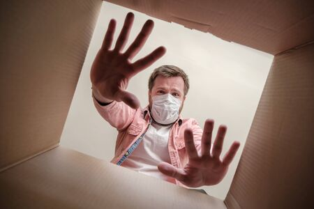 Frightened man in a medical mask unboxing inside view a delivered box, shows a stop gesture with hands afraid of virus. Paranoia.