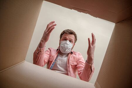 Astonished man in medical mask unboxing inside view a delivered box. Concept of caution and protection during a virus outbreak.