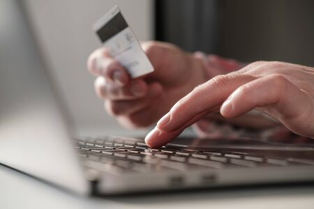 Hands enter bank details of a credit card on a laptop to pay for online purchases. Concept of self-isolation. Modern lifestyle.