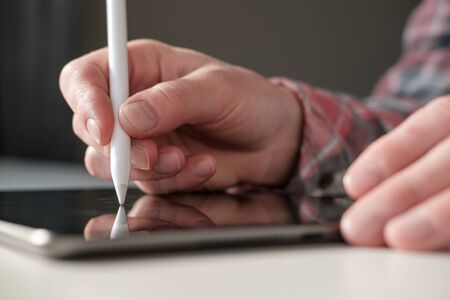 Hand writes or draws with stylus pen on a digital tablet. Close-up.