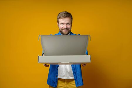 Joyful man came to a meeting with friends with a pizza, he smiles and holds out an open box from which there is a seductive aroma.
