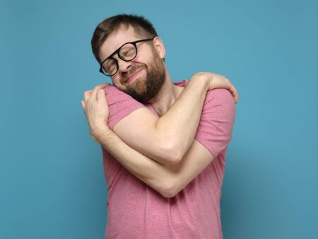 If you are single, hug yourself. Funny, cute bearded man in glasses cuddling himself and dreams with eyes closed. 스톡 콘텐츠