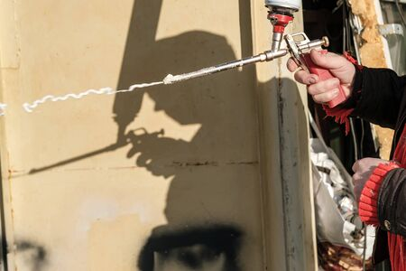 Male hands are holding an old professional gun for aerosol insulating foam, with a balloon and checking its work, outdoors.