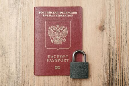 Passport with a padlock. Concept of banning visits to other countries during a pandemic. Symbol of restriction of travel. Top view.