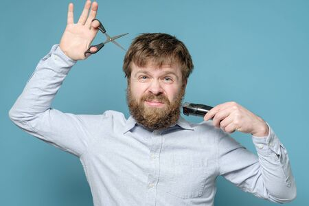 Excited shaggy man with scissors and a trimmer in his hands had not been in the barbershop for a long time. Concept of quarantine.