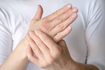 Une femme a mal à la main et masse un point sensible contre un tee-shirt blanc. Banque d'images