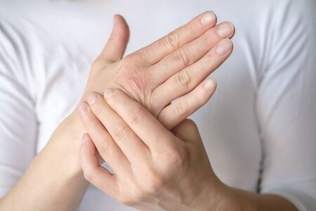 Woman experiences pain in her hand and is massaging a sore spot against a white tee-shirt. Stock Photo