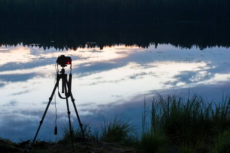 Camera on a tripod on the shore of a forest lake, takes a picturesque night landscape.