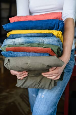 Woman in a white t-shirt holds in her hands neatly folded in a stack of trousers and jeans of bright colors, after washing.