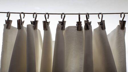 Weißer Vorhang hängt an Metallwäscheklammern, in natürlichem Licht aus einem Fenster. Standard-Bild