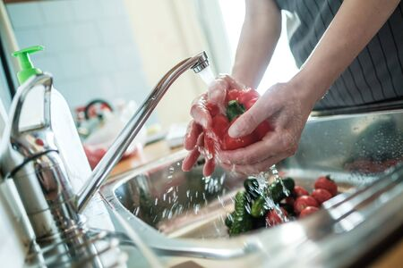 Female hands wash red pepper under a stream of water, against the background of vegetables in the sink. Cooking food.
