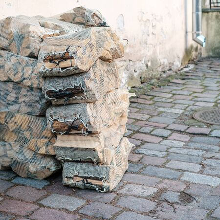 Dry firewood in a grid, stacked in a pile, lie on the street of the ancient city, near the wall.