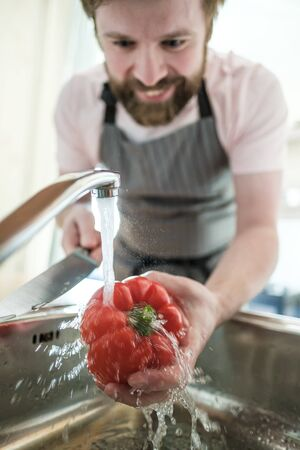 Male hand holds red pepper under a stream of water, and in another knife. Man in an apron is preparing for cooking, in the kitchen. Standard-Bild