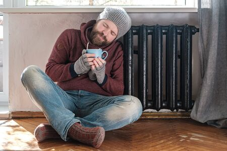 Man in a hat and gloves leaned against the radiator while sitting on the floor, he holds a mug of hot drink and enjoys the warmth. Standard-Bild